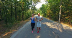 Couple jogging along road in forest Stock Footage