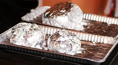 Cooking of potatoes on gas and stone grill wrapped in aluminum foil Stock Footage