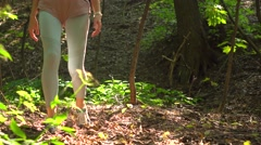 Slender girl with backpack hiking in the woods. 4K steadicam tracking shot Stock Footage