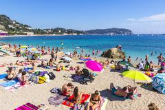 Crowded summer beach in Villefranche-sur-Mer, Nice, France Stock Photos