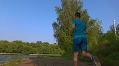 Young man running on sandy summer riverside, back view. 4K zoom in video Stock Footage