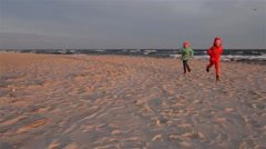 Two sisters walking along shore of Baltic Sea Stock Footage