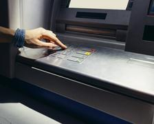 Female hand entering the secret code in the ATM at night on the street Stock Photos