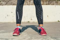 Close-up of athletic female legs in red sneakers on a concrete pad outdoors i Stock Photos