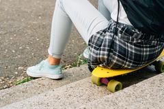 Girl in white T-shirt and jeans sitting on the yellow plastic skateboard Stock Photos