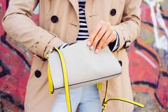 Woman in beige coat and jeans holding a lady's handbag on a background of gra Stock Photos