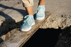 Female feet in beige pants and sneakers are on the board over the precipice Stock Photos