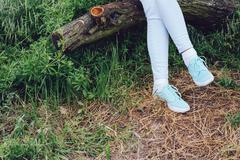 Female feet in sneakers and jeans on a log in the forest Stock Photos