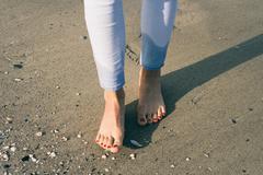 Bare female feet walking on wet sand at beach Stock Photos