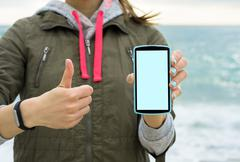 Girl in the green jacket on the beach showing the mobile phone screen Stock Photos