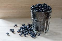 Blueberries in a glass with scattered berries. Good addition for breakfast - stock photo