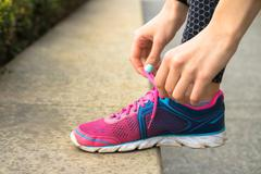 Female hands with manicure tie laces on pink and blue sneakers while jogging  Stock Photos