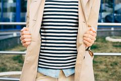 Woman in a striped T-shirt, denim shirt and an unbuttoned beige coat outdoors Stock Photos