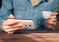 Woman in a denim shirt reading news on mobile phone and drinking coffee Stock Photos