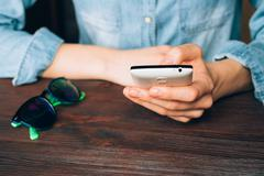 Woman in a denim shirt holds a mobile phone and sitting at a wooden table on  Stock Photos