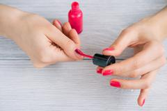 Women's hands painted nails with red lacquer, close-up Stock Photos