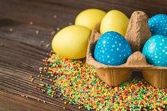 Yellow and blue easter eggs in a box on a wooden table Stock Photos