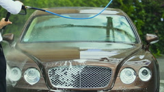 Car wash employee servicing expensive business class auto, using water spray gun Stock Footage