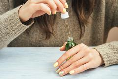Woman in a brown sweater with yellow manicure holding a green bottle with cos Stock Photos
