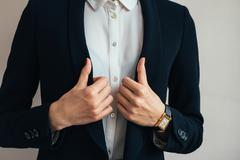Woman wears a business suit jacket. In her hand wristwatch Stock Photos