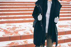 Young slim woman in unbuttoned black coat, a gray sweater and gloves walking  Stock Photos