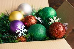 Christmas decoration in a cardboard box on a wooden background closeup Stock Photos