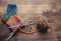 Knitted sock, ball of yarn and knitting needles on a wooden surface Stock Photos
