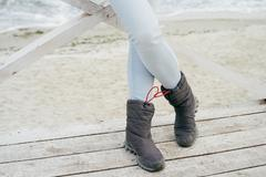 Female feet in blue jeans and sporting boots standing on a wooden platform on - stock photo