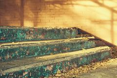 Old concrete steps and fallen leaves in sunlight outdoors closeup Stock Photos
