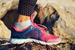 Female foot in pink and blue sneaker standing on rocky stones sunny morning Stock Photos