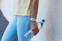 Bottle of drinking water in a female hand closeup Stock Photos