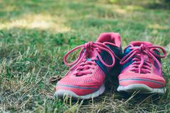 Pink and blue sneakers on a green grass Stock Photos