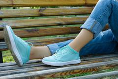 Female feet in jeans and sports shoes on a bench close-up Stock Photos