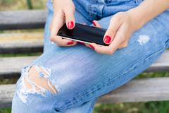 Female hands with red manicure holding a cell phone with a touch screen Stock Photos
