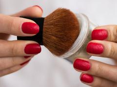 Brush and powder in female hands Stock Photos