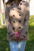 Young girl in a beige coat, blue jeans and striped t-shirt - stock photo
