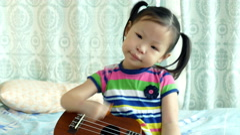 Girl playing ukulele at home Arkistovideo
