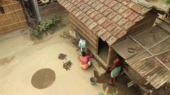 Woman washes her courtyard in Bengal, India. Wide shot, rotating to show othe Stock Footage