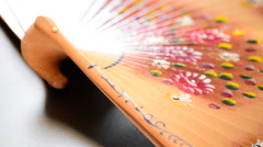 Hand fan in wood decorated with flower gyrating Stock Footage