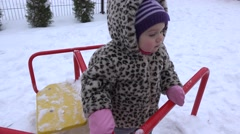 Happy baby girl having fun on swing ride at winter playground. 4K - stock footage