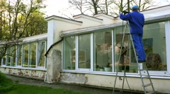 Man on ladder with high pressure washing tool clean glass house in nature Stock Footage