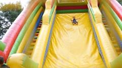 Happy childhood - little kid girl slides down inflatable slide park trampoline Stock Footage