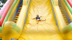 Happy childhood - little kid girl slides down inflatable slide park trampoline Stock Footage