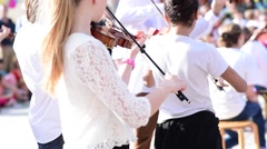 Slow motion of Kids play violin at outdoor performance group Stock Footage