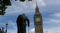 Statue of Sir Winston Churchill overlooking The Elizabeth Tower (big Ben) Parlia Stock Footage