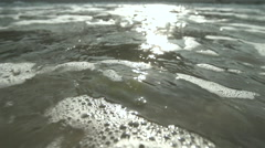 Sea wave splashing and forms bubbles under the surface of the water in slow Arkistovideo