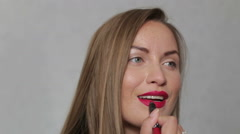 Beautiful girl paints her lips Stock Footage