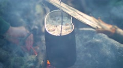 Breakfast in the campaign. Cauldron over the fire. The fire heats the food Stock Footage