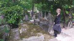 Woman Stands at Cross Grave Stock Footage