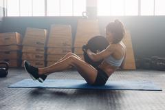 Energetic woman doing abdominal exercise Stock Photos